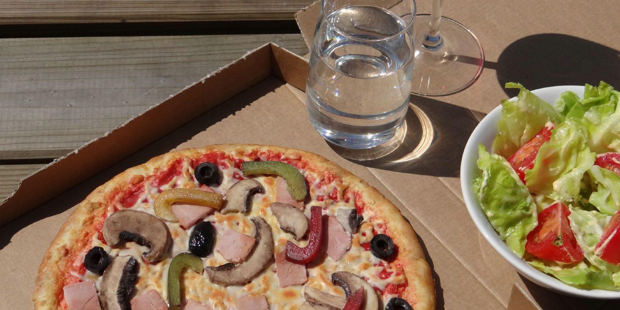 fausse pizza faite en résine accompagnée de sa salade factice et de ses fausses boissons