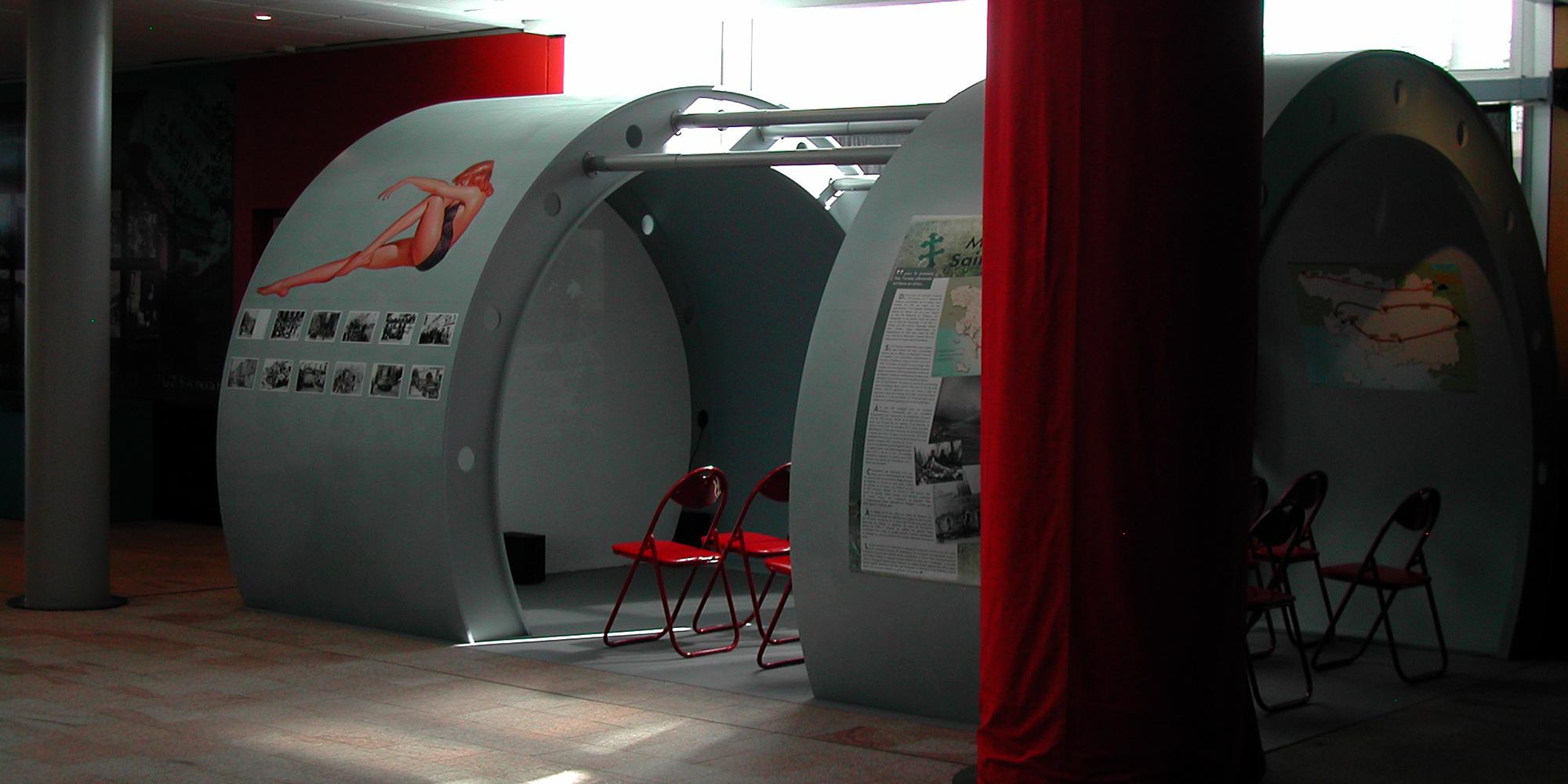 création d'un décor d'exposition suggérant la carlingue un avion bombardier avec peinture de pin-up et projection vidéo