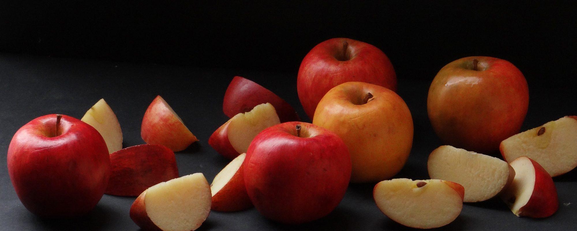 un gros plan sur des pommes factices entières et coupées qui sont réalisées en résine