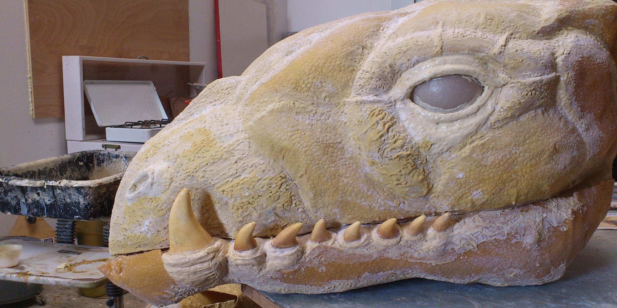 étape de travail de sculpture de tête de dragon avec positionnement des dents en résine et effets de texture de peau de reptile